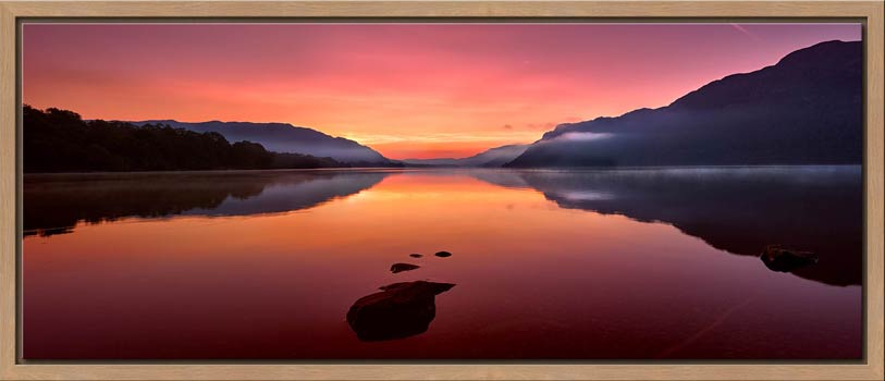 The mists and golden light of sunrise over a becalmed Ullswater at dawn