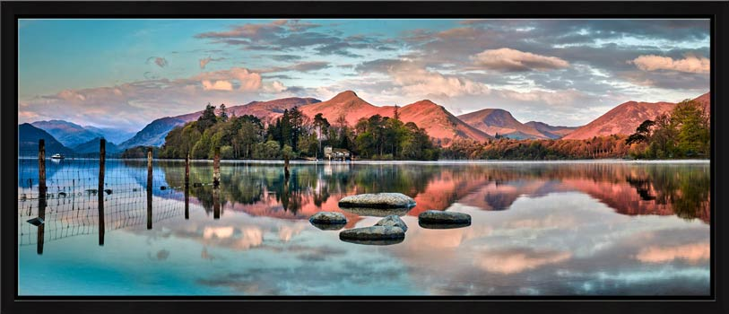 The early morning spring sunlight gives a red hue to the mountains around Derwent Water